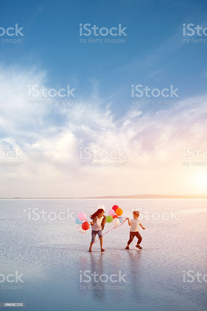Little children play with color balloons on the water - Photo