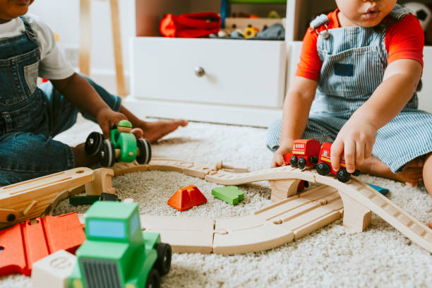 Little children playing with a railroad train toy Little children playing with a railroad train toy bib overalls boy stock pictures, royalty-free photos & images