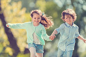 Two smiling kids holding hands and having fun in nature.