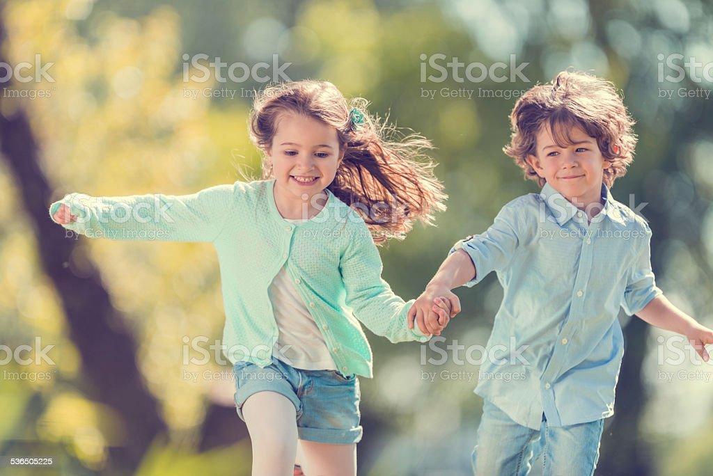 Little children running in the park. stock photo