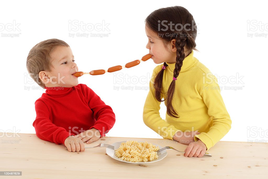 Little children sharing the chain of sausages royalty-free stock photo