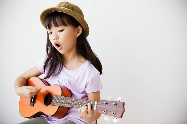 little chinesische mädchen singen und spielen ukulele - ukulele songs stock-fotos und bilder