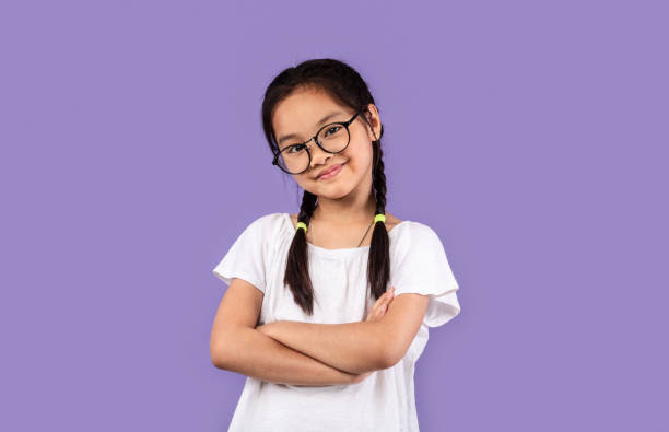 Little Chinese Girl Wearing Eyeglasses Posing Crossing Hands, Purple Background stock photo