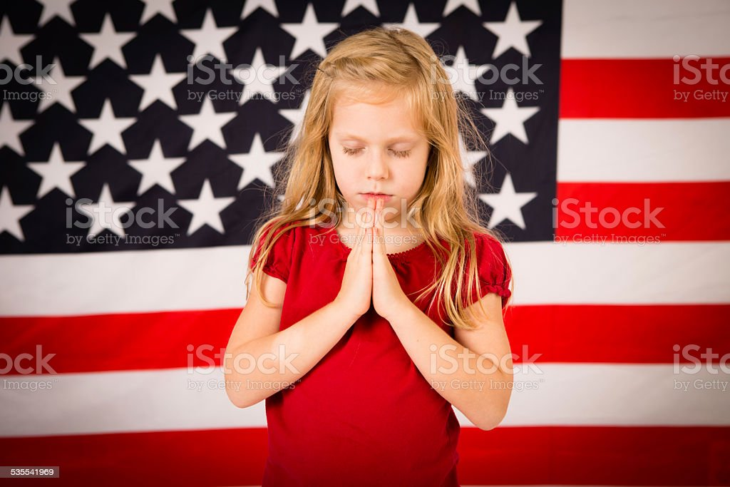 Little Christian Girl Praying in Front of American Flag stock photo