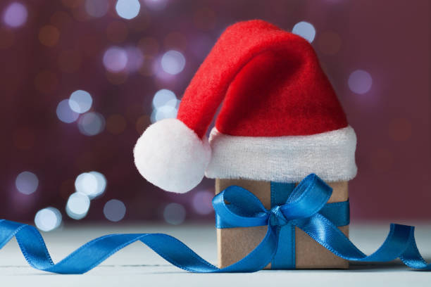 Royalty free blue magic santa hat pictures images and stock photos little christmas gift box or present and santa hat against magic bokeh background holiday greeting m4hsunfo Images