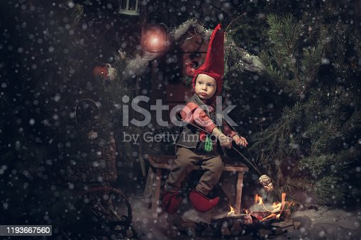 Stock studio photo with white background of a baby disguised elf with hands on the head cap rolled from Christmas balls