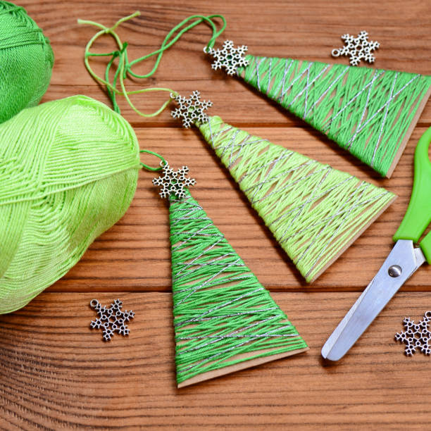 kleine weihnachtsbäume sind aus karton, baumwollgarn und verziert mit kleinen metall schneeflocken. einfach und billige weihnachten basteln für kinder machen. erschwingliche christmas crafts - kinder die schnell arbeiten stock-fotos und bilder