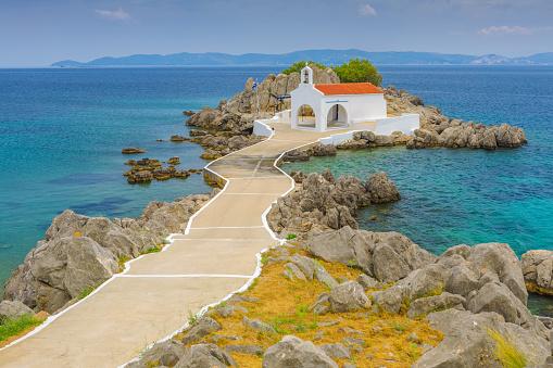 classical white greek church on a small rocky island in Agios Isidoros, Greece