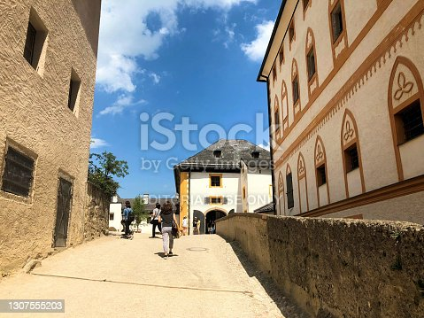 People are walking along a small way between two buildings with a wall on the right side on a sunny day at the historic old castle in Salzburg in Austria June 10,2018