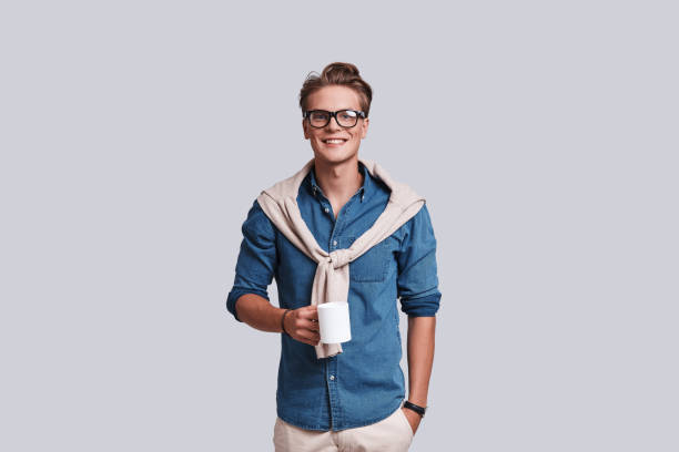 Little coffee break. Handsome young man looking at camera and holding a cup while standing against grey background smart casual stock pictures, royalty-free photos & images