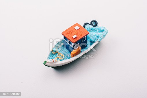 Little colorful model fishing boat placed on white