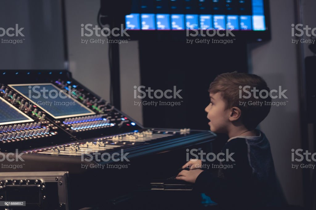 Small sound engineer learning do edit music and adjust volume on...