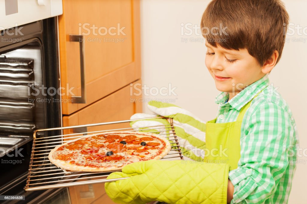 Little cook preparing tasty pizza in the kitchen royalty-free stock photo