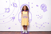 Cheerful cute African girl dreaming to be cosmonaut, she standing in exposure suit outer space drawing on white wall