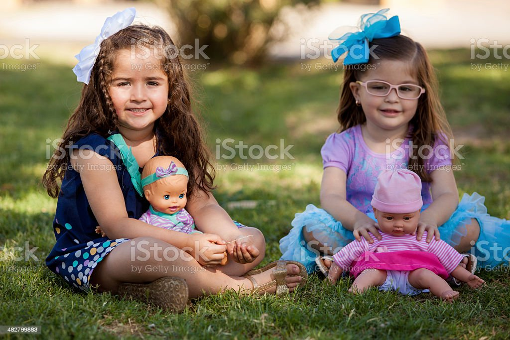 Little cousins playing with dolls stock photo