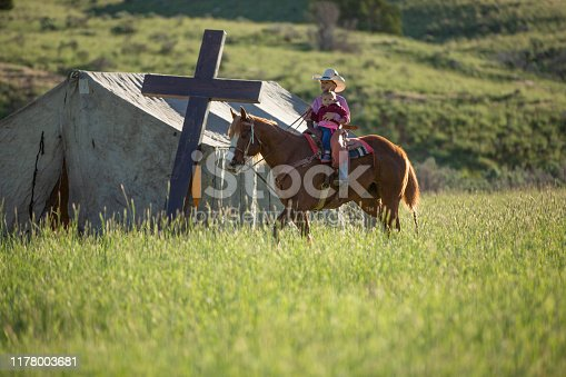 Little cowboy and sister horseback riding by a small tent church in a ranch