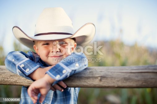 A young American cowboy smiles.