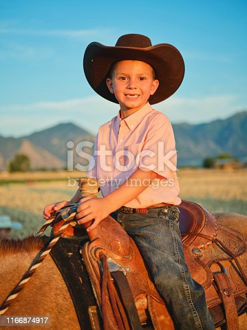 A young cowboy boy child with his pony horse on a ranch in Utah, USA.