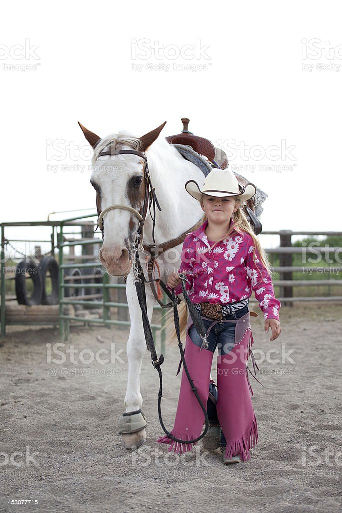Little Cowgirl Walking Horse with White Sky Background royalty-free stock photo