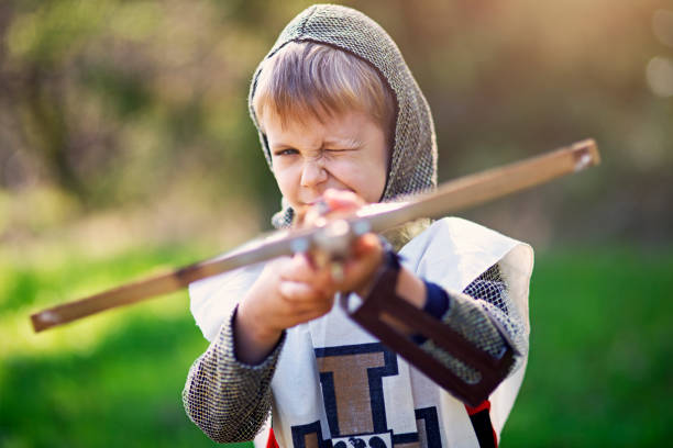 little crossbowman aiming at the camera - crossbow stock pictures, royalty-free photos & images