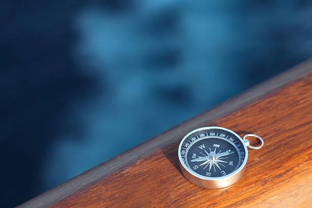 Little cruise compass on wooden rail stock photo