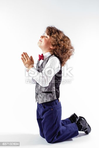 istock Little curly boy in vest kneeling and asking a blessing. 637132834