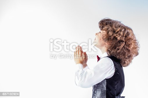 istock Little curly boy with hands folded in prayer, looking upwards 637132924