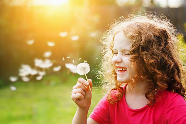 Wenig geschweiften Mädchen Blasen Löwenzahn und viel miteinander lachen. – Foto