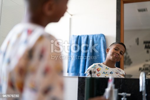 istock Little Cut Kid Looking to the mirror at morning 982976230