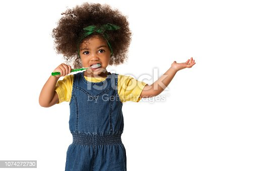 A little cute african american girl brushing her teeth, isolated over white background. Healthy teeth concept.
