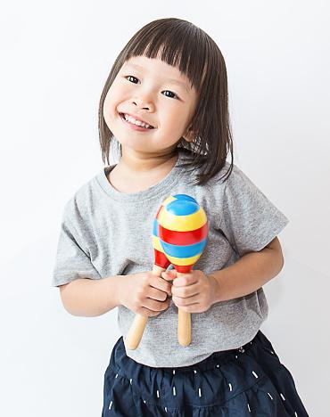 Little cute asian girl playing the maracas, preschool play group