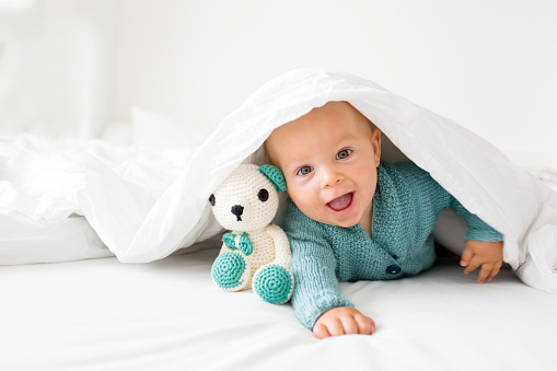 Little cute baby boy, child in knitted sweater, holding knitted toy, smiling happily at camera in white sunny, bright bedroom