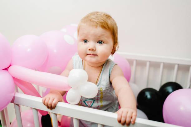kleine süße baby mädchen prinzessin säugling 1-2 jahr stehend und spielen auf dem bett zu hause dekoriert farbige luftballons für geburtstagsparty. glückliches baby für einen urlaub. feier erstes jahr konzept. - lila mädchen zimmer stock-fotos und bilder