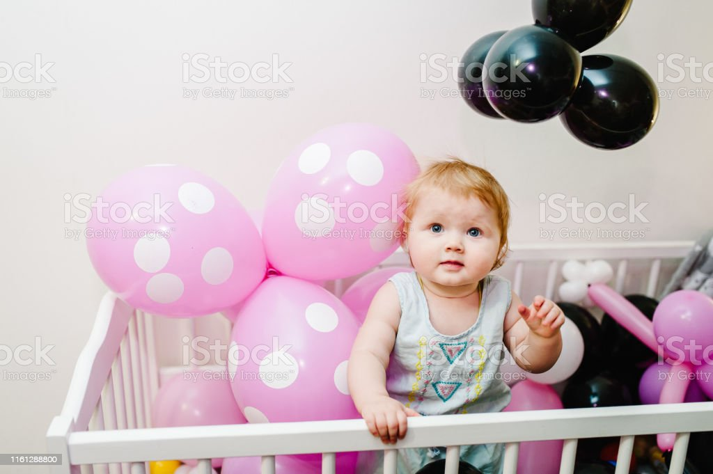 Little Cute Baby Girl Princess Jumps On A Bed And Playing With Colored Air Balloons Having Fun Grabbing Family New Life Childhood Beginning Concept