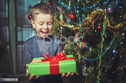 christmas, holidays and childhood concept - smiling child with gift box at home