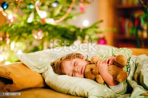 915609494 istock photo Little cute blond boy sleeping under Christmas tree and dreaming of Santa at home, indoors. Traditional Christian festival. Happy kid child waiting for gifts on xmas. Cozy soft light 1192100719