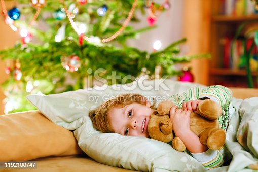 915609494 istock photo Little cute blond boy sleeping under Christmas tree and dreaming of Santa at home, indoors. Traditional Christian festival. Happy kid child waiting for gifts on xmas. Cozy soft light 1192100747