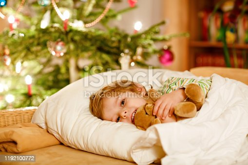 915609494 istock photo Little cute blond boy sleeping under Christmas tree and dreaming of Santa at home, indoors. Traditional Christian festival. Happy kid child waiting for gifts on xmas. Cozy soft light 1192100772