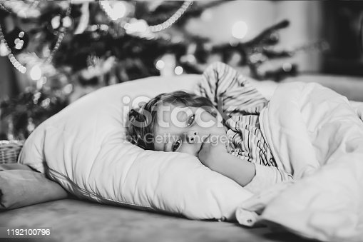 915609494 istock photo Little cute blond boy sleeping under Christmas tree and dreaming of Santa at home, indoors. Traditional Christian festival. Happy kid child waiting for gifts on xmas. Cozy soft light 1192100796