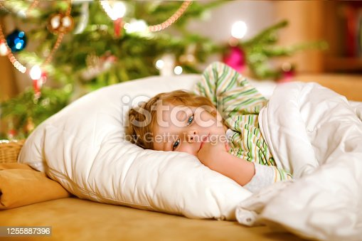 915609494 istock photo Little cute blond boy sleeping under Christmas tree and dreaming of Santa at home, indoors. Traditional Christian festival. Happy kid child waiting for gifts on xmas. Cozy soft light 1255887396