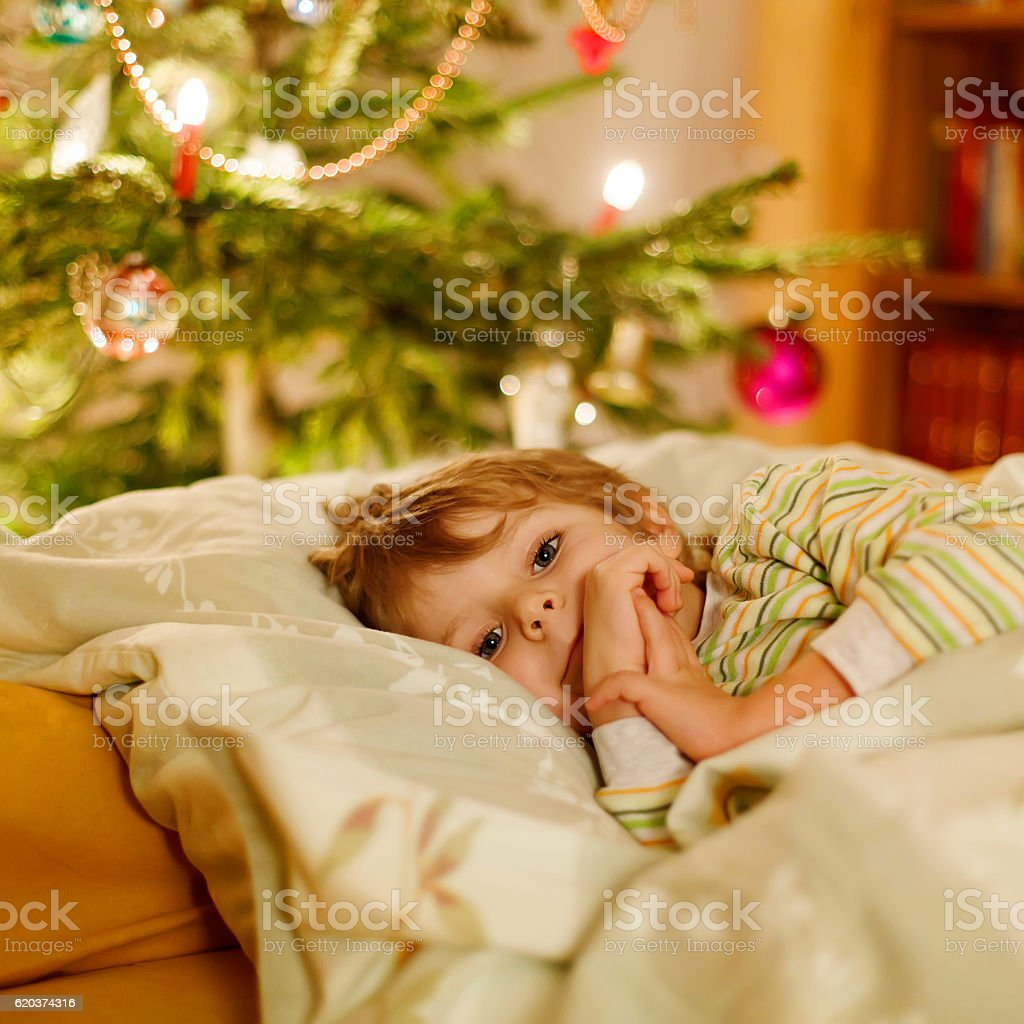 Pequeno bonito rapaz loiro dormir sob a Árvore de Natal foto de stock royalty-free