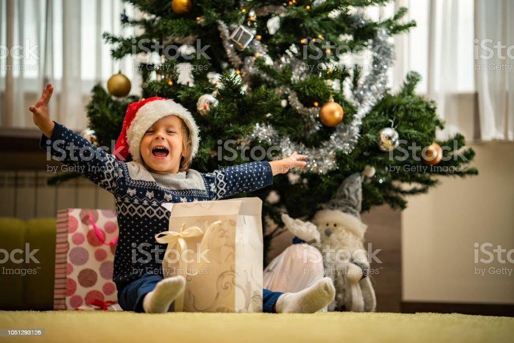 Portrait cute boy opening Christmas present sitting on the floor
