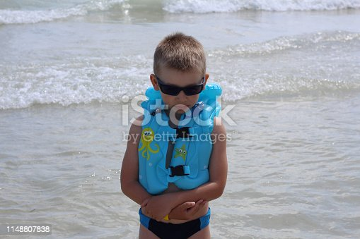 Little cute boy looks unhappy on the beach. The boy was offended by his parents in the summer on the beach. Sad boy at the sea. Vacation at sea with children.