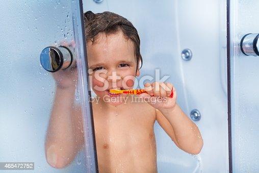 istock Little cute boy use toothbrush in shower cabin 465472752