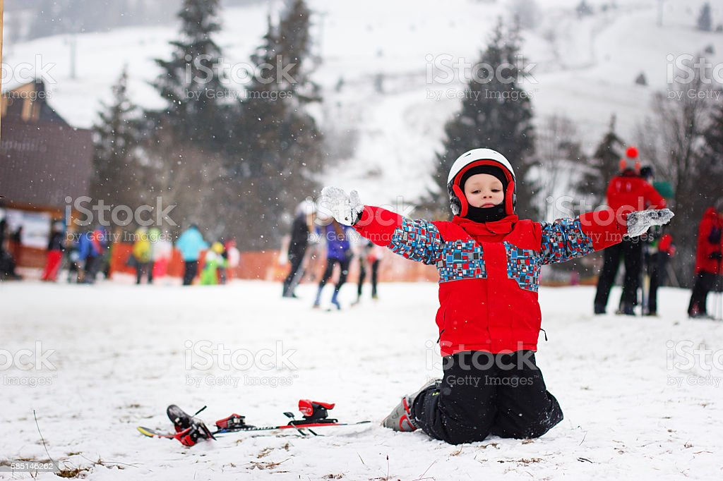 Little cute boy with skis and a ski outfit. stock photo