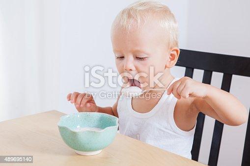 istock Little cute child boy eating yogurt himself, morning breakfast 489695140