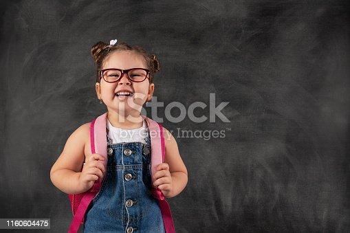 istock Little cute child holding school bag on blackboard.Education concept. 1160604475