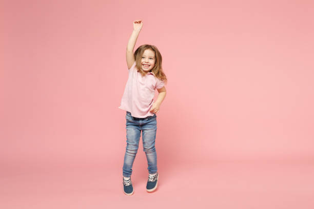 Little cute child kid baby girl 3-4 years old wearing light clothes dancing isolated on pastel pink wall background, children studio portrait. Mother's Day, love family, parenthood childhood concept. stock photo