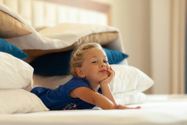liten söt flicka byggt improviserad fort (slott, hus) av kuddar och filtar på sängen. barn handgjorda tältstuga - fort bildbanksfoton och bilder