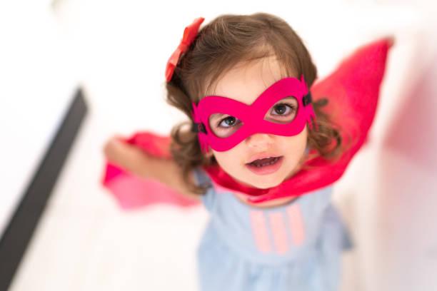 liten söt flicka dressing som en superhjälte porträtt - superwoman barn bildbanksfoton och bilder